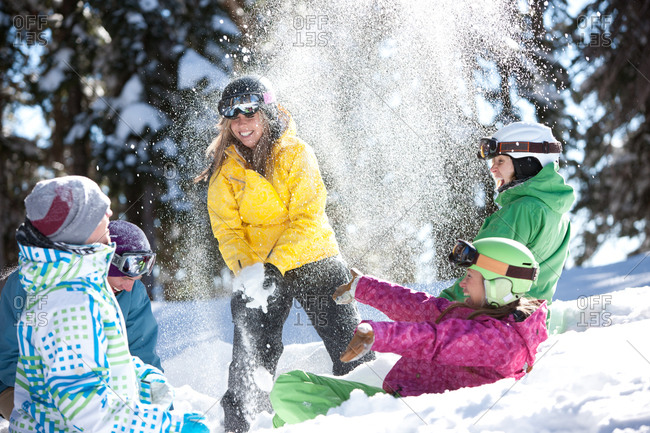 A playful group of snowboarders enjoy an unbridled moment of fun in the snow.