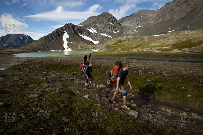One man and one woman packrafting / hiking in big mountains by a lake.