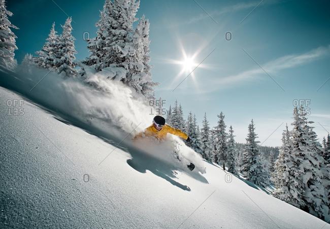 A snowboarder glides through untracked powder.