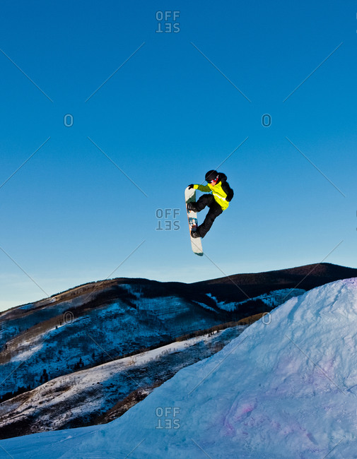 A snowboarder launches into the twilight sky.