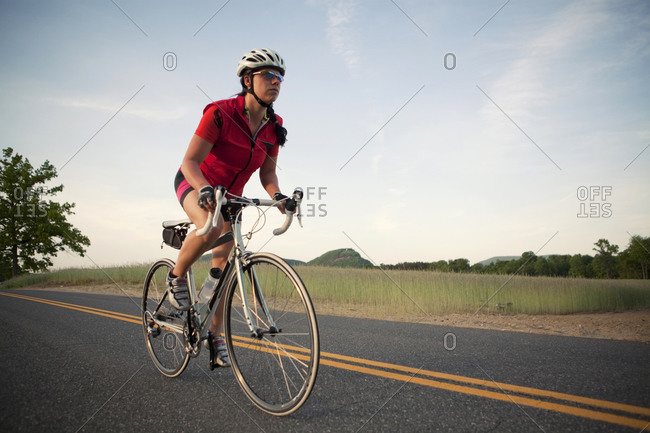A female cyclist rides on a rural country road in New England.