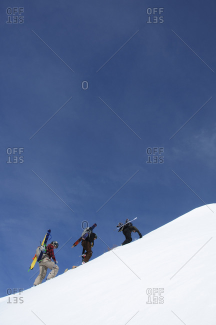 A crew of three climbing to the trail.
