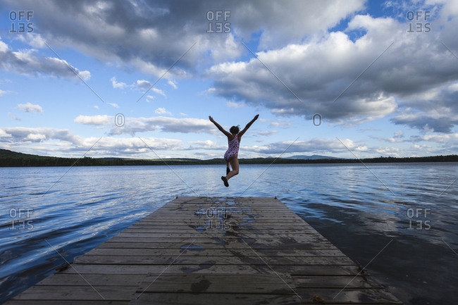 A young girl jumping off of a dock at Spencer Pond in northern Maine.