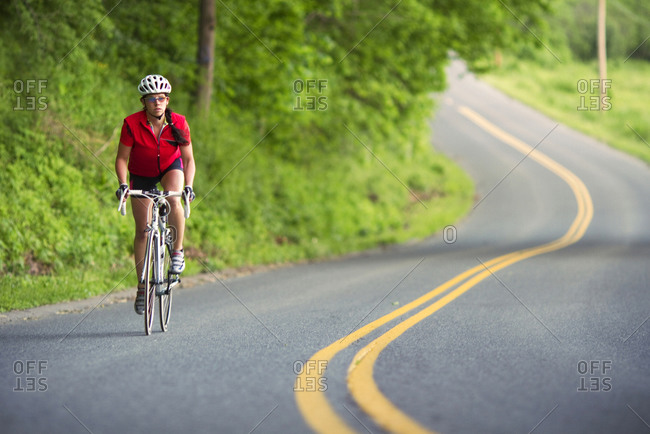 A female cyclist rides along a country road.
