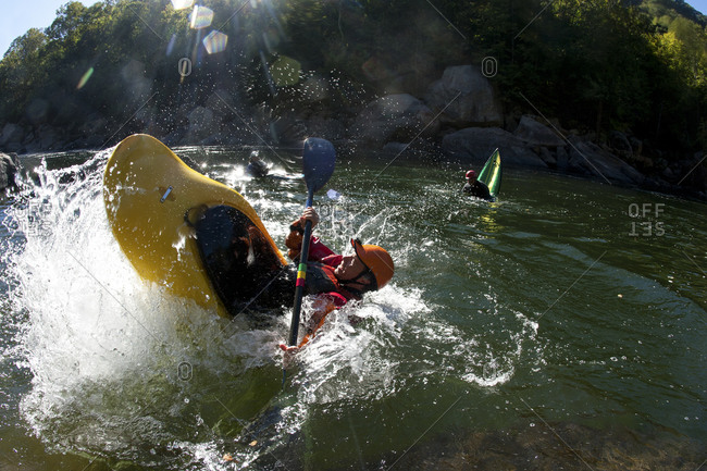 Overhead view of two kayakers doing tricks on a river in flat water.