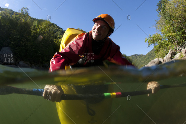 Split level view of one man smiling and doing a bow stall in his kayak.