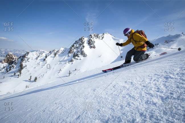 One male telemark skier skiing by.
