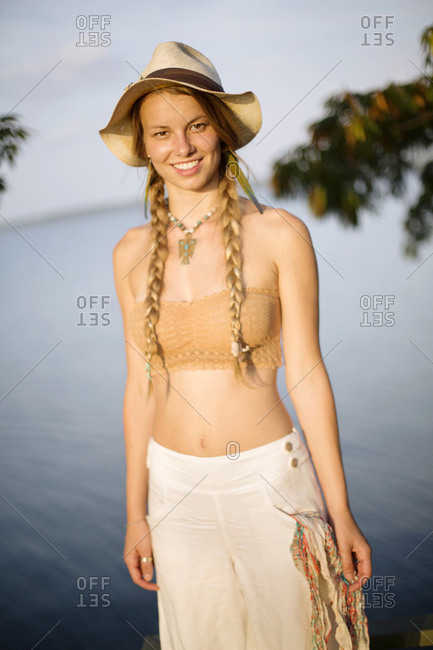 A young woman with braids smiles while looking at the camera.