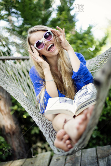 A young woman wearing colorful glasses sitting in a hammock laughs while reading a book.
