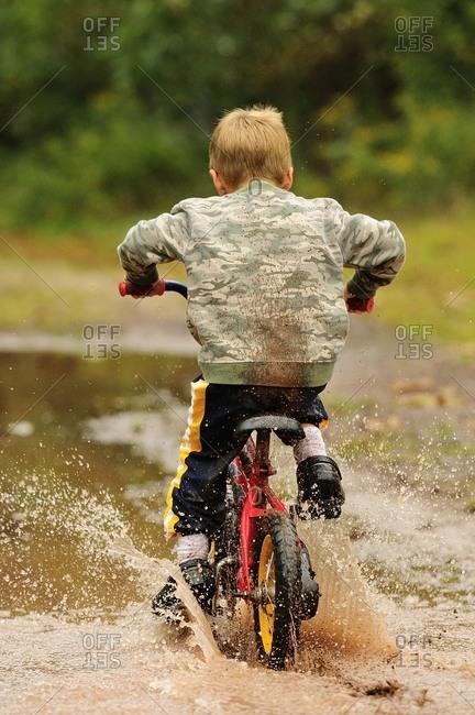A little boy riding bike off through the mud.