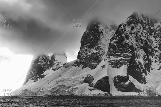 Dramatic Antarctic sky above water and mountain in black and white