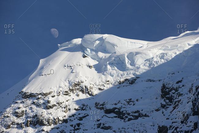Moon above hilltop in daytime in Antarctica