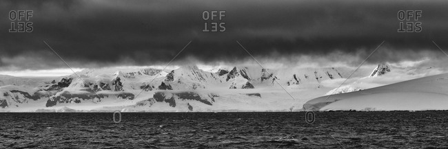 Dramatic Antarctic sky above water and landscape in black and white