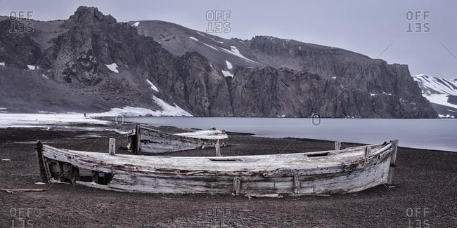 Old weathered boats on seashore on Deception Island, Antarctica
