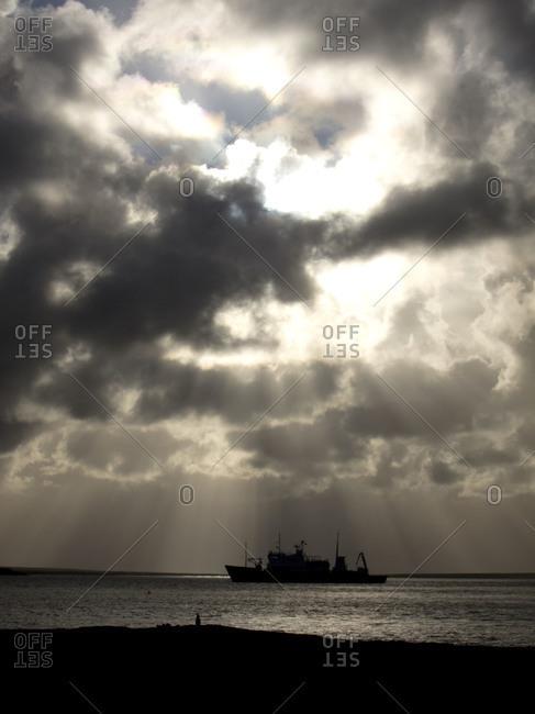 Silhouette of Polar Pioneer ship in dramatic lighting