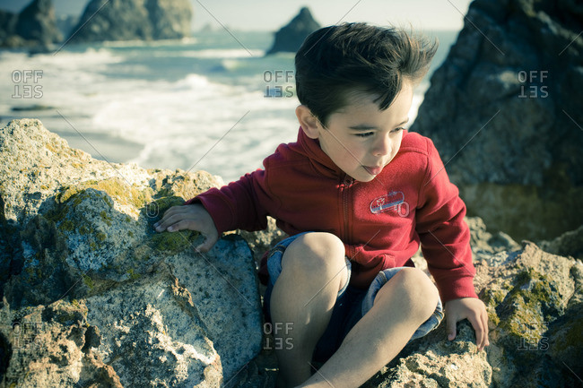 Little Boy Sitting on Rocks at the Beach, Harris Beach State Park, Brookings, Oregon, USA