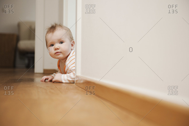 Baby Lying on Floor Peeking Around a Corner