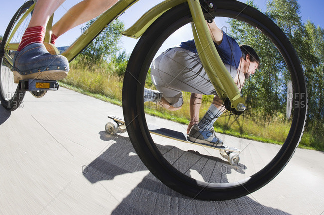 Woman Riding a Bicycle and Man Riding a Skateboard on a Bike Path, Steamboat Springs, Routt County, Colorado, USA