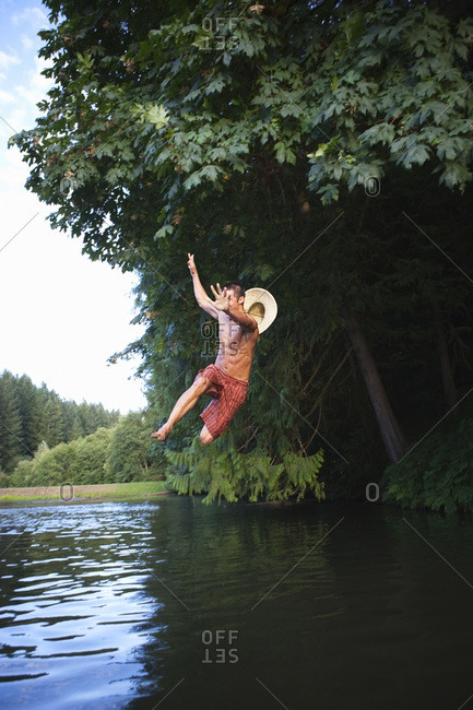 Teenage Boy Jumping Into Lake, Near Portland, Oregon, USA