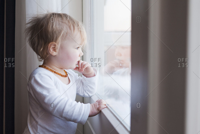 Portrait of Baby Girl Looking out Window