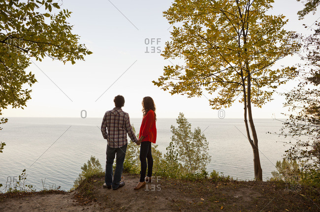 Backview of Young Couple Standing at Edge of Cliff Looking out at View, Ontario, Canada