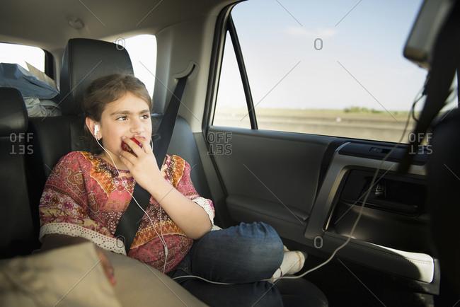 Girl eating apple in car