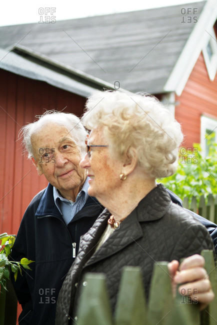 Pensioners in front of red cottage