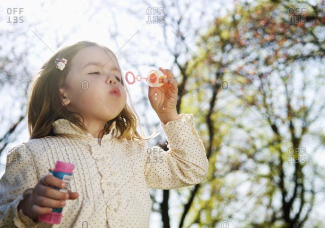 Little girl blowing bubbles - Offset