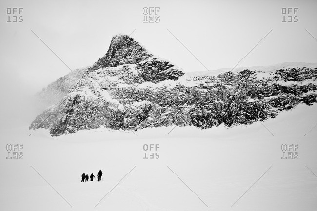 Four people hiking in snow capped mountain in winter