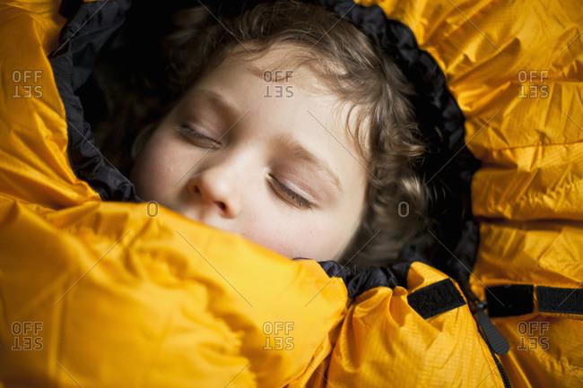 Little girl resting inside sleeping bag