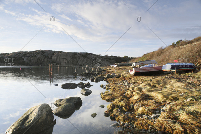 Nautical boats lying upside down on side of lake