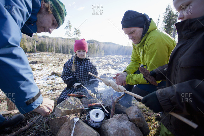 Men cooking while children looking at camping site