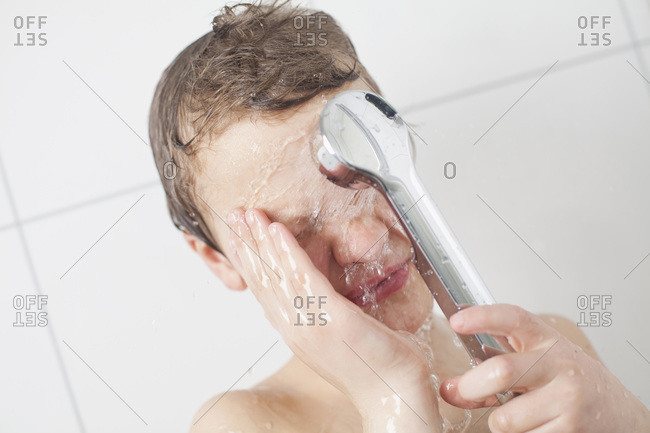 Young boy bathing with shower head in bathroom