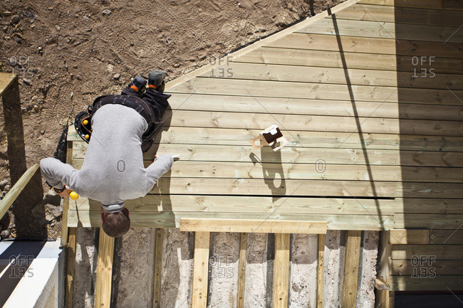 High angle view of manual worker using drill on floorboard