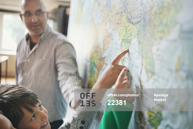 Mature male professor assisting schoolboys studying world map in classroom