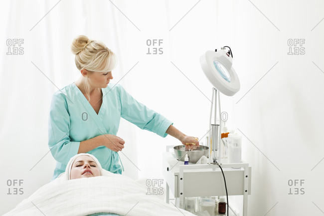 Blond beautician taking something from a bowl while customer lying on massage table in beauty spa