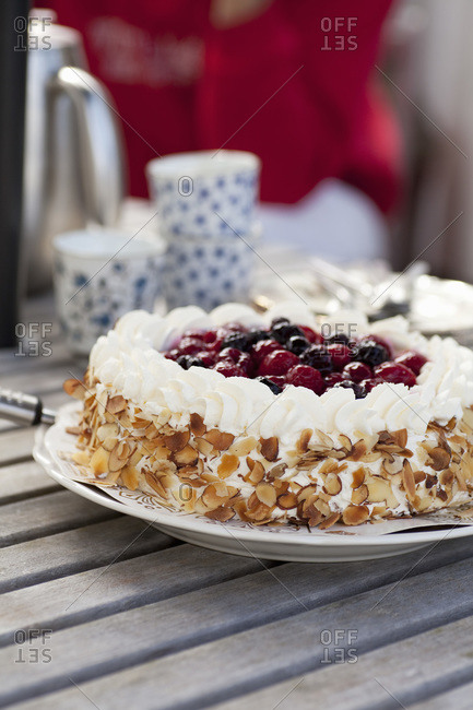 Fresh cake with berry fruit topping served in plate on wooden table