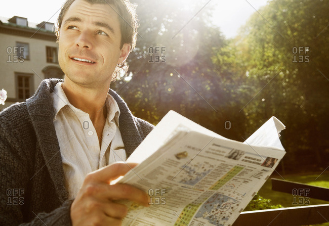 Man sitting outside reading - Offset