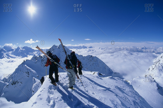 Two people with skis on mountain in winter