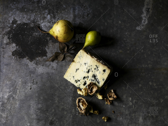 Blue cheese, pears and some peeled walnut on a gray kitchen counter.