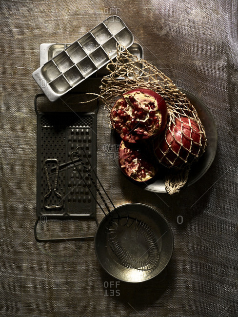 Still-life of ice cube tray, opened pomegranate in net, a vintage grater, whisk and metallic bowls.