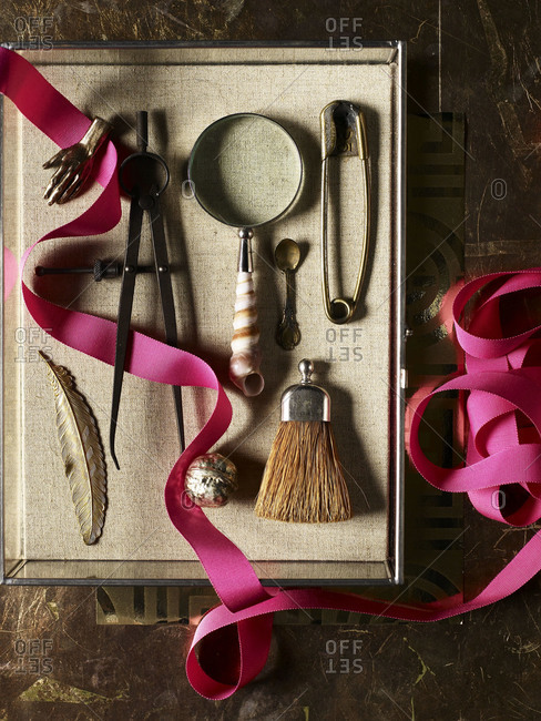 Magnifying glass with shell handle, safety pin, caliper, brooches and a small brush.