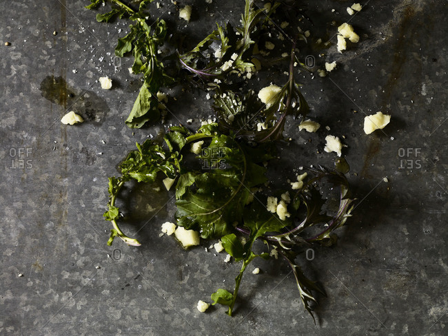 Close-up of parmesan crumbs with leafy greens.