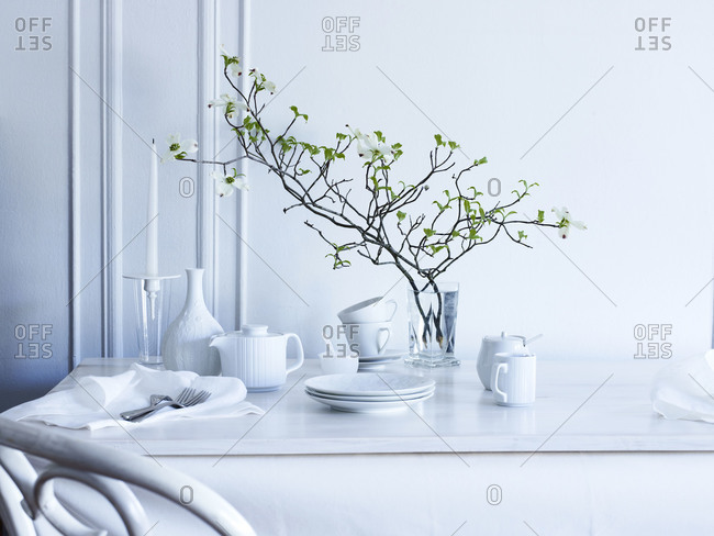 White table with serve-ware in a white interior.