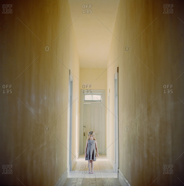 Girl standing in house corridor and looking at camera