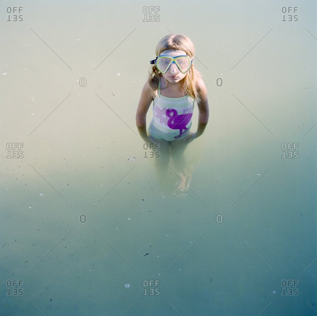 Girl standing in water and wearing scuba mask