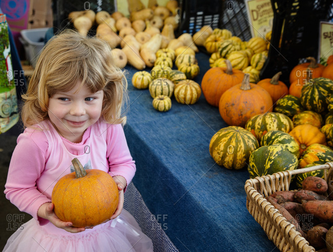 Cute little girl wearing pink ballet dress, carrying a sugar pumpkin at farmer's market