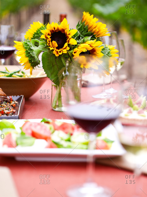Set table with a beautiful bunch of sunflowers in the vineyard
