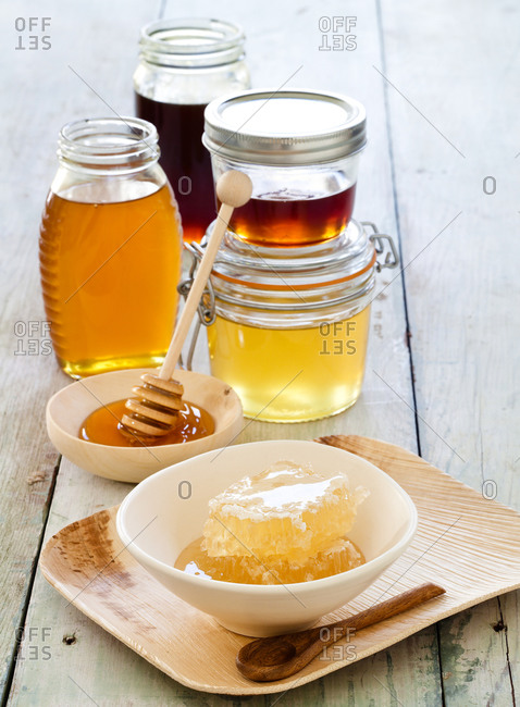 Different jars of honey, honeycombs and wooden drizzler