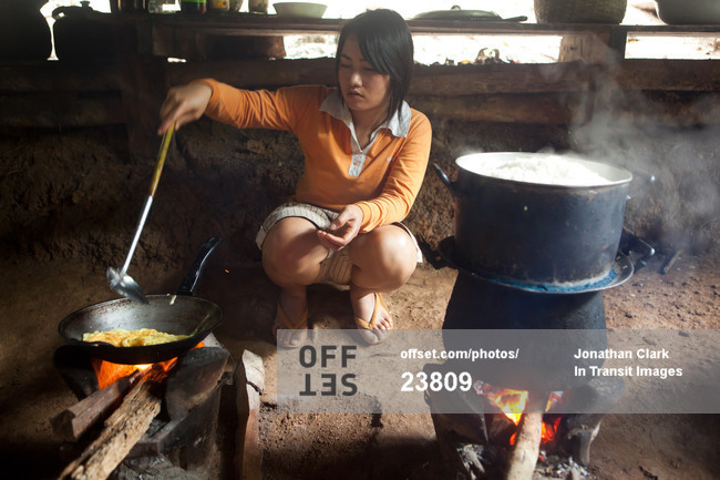 Woman Cooking A Meal Over An Open Fire In Laos